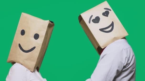 pojmu emoce, gesta. pár lidí se papírové sáčky na hlavách, s malovanými emotikonu, úsměv, radost, oči v lásce