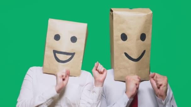 pojmu emoce, gesta. pár lidí s batohy na jejich hlavy, s malovanými emotikonu, úsměv, radost, smích