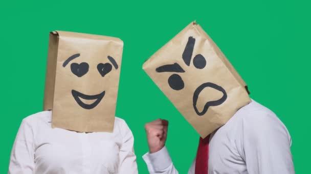 Pojem emoce a gesta. Dva lidé v papírových taškách s úsměvem. Přísahá, že agresivní smajlík. Druhý se dívá na něj v očích lásku