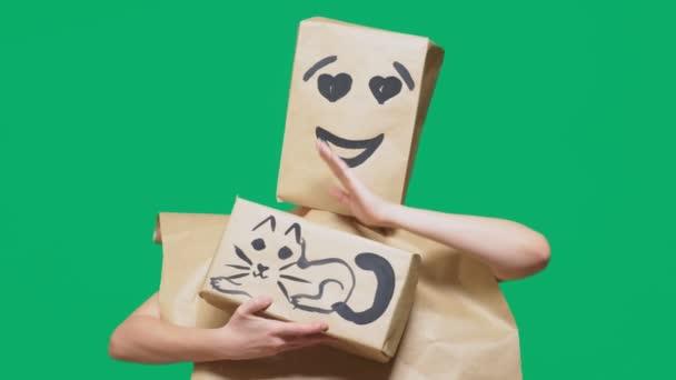 pojmu emoce, gesta. muž s balíčkem na hlavě, s malovanými emotikonu, úsměv, milující oči. hraje s kočkou na pole.