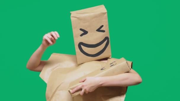 pojmu emoce, gesta. muž s balíčkem na hlavě, s malovanými emotikonu, úsměv, radost, smích. hraje si s dítětem malované na box.