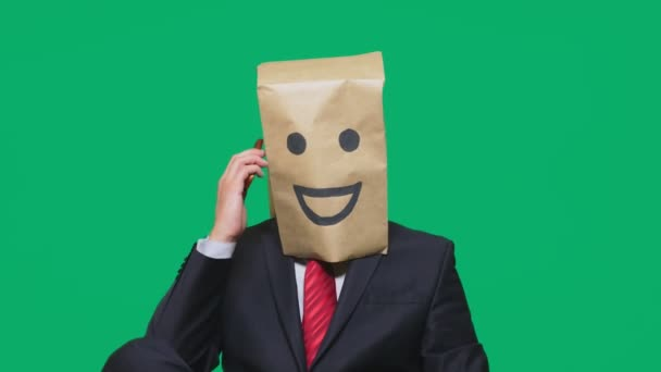 concept of emotions, gestures. a man with paper bags on his head, with a painted emoticon, smile, joy. talking on a cell phone.