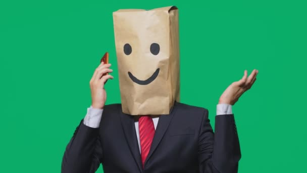 concept of emotions, gestures. a man with paper bags on his head, with a painted emoticon, smile, joy. talking on a cell phone