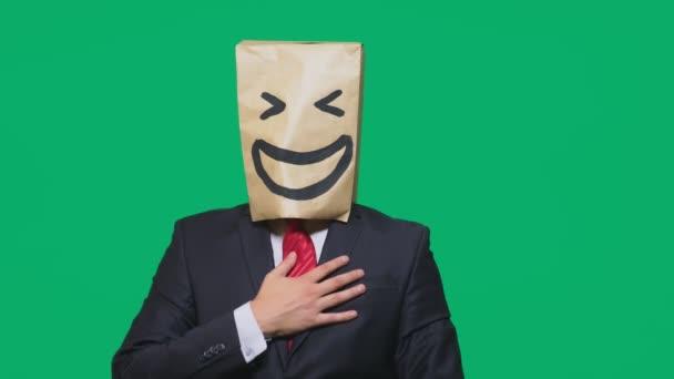 pojmu emoce, gesta. muž s papírové sáčky na hlavě, s malovanými emotikonu, úsměv, radost