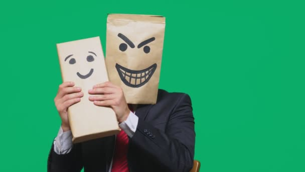 concept of emotions, gestures. a man with a package on his head, with a painted emoticon devil, crafty, gloating. plays with the child drawn on the box. childs deception, naivety