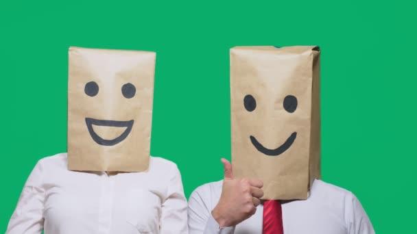 pojmu emoce, gesta. pár lidí s batohy na jejich hlavy, s malovanými emotikonu, úsměv, radost, smích.