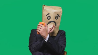 concept of emotions, gestures. a man with paper bags on his head, with a painted emoticon, fear.
