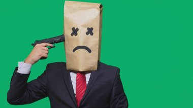 concept of emotion, gestures. a man with a package on his head, with a painted smiley, exhausted, tired, Holds a gun in his hand. The concept of suicide.