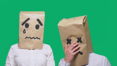 concept of emotions, gestures. a couple of people with bags on their heads, with a painted emoticon, sad, crying, tired