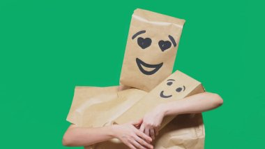 concept of emotions, gestures. a man with a package on his head, with a painted emoticon, smile, enamored eyes. plays with the child painted on the box.