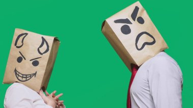 concept of emotions, gestures. a man with a package on his head, with a painted emoticon, one angry screaming, another crafty, and the devil laughs. trolling, lies, provocation