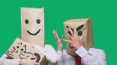 The concept of emotions and gestures. Two people in paper bags with smileys. Aggressive smiley swears. The second smiles at him and strokes the cat painted on the box.