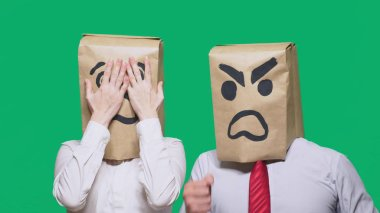 The concept of emotions and gestures. Two people in paper bags with smileys. Aggressive smiley swears. The second crying sad