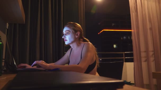 young woman with cosmetic mask on face working with laptop at home in the evening. naturalness