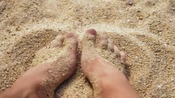 Pánské nohy na mořském písku a vlny, relaxace na oceán pláž, letní prázdniny.