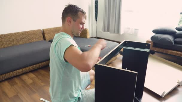 A young man independently collects furniture in the living room of his house. A man collects a computer desk.