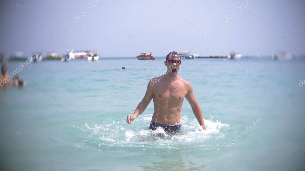 a young man dives into the sea wearing sunglasses. emerges and smiles