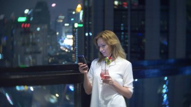 Young woman blonde relaxing and drinking cocktail in bar with a view of the skyscrapers at night. background blur