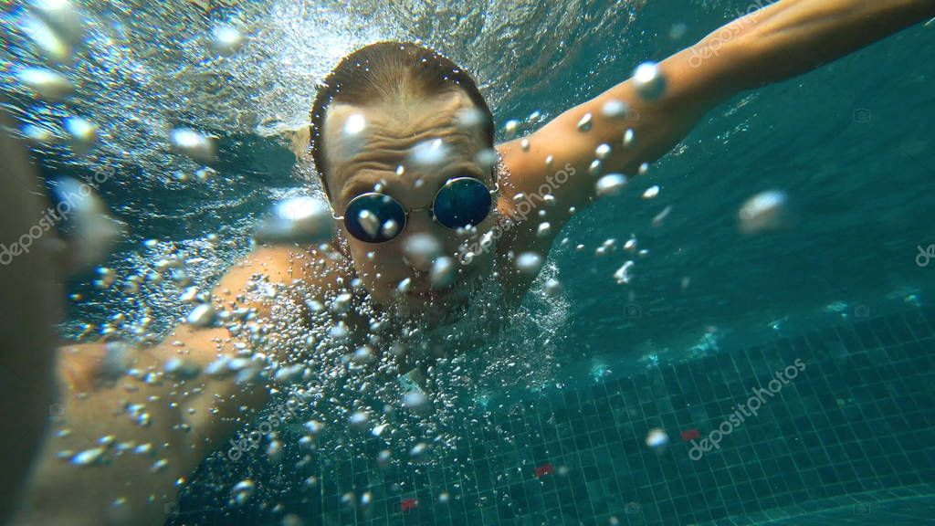A young white handsome male doing an underwater selfie on an action camera. Portrait of a young man with glasses taking himself off to the camera under water.
