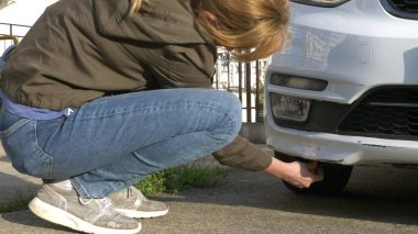 looking at a damaged vehicle. Woman inspects car damage after an accident