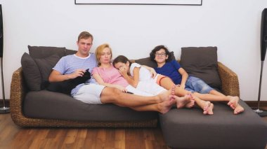 Charming family, mom, dad, daughter and son are watching TV in the living room together