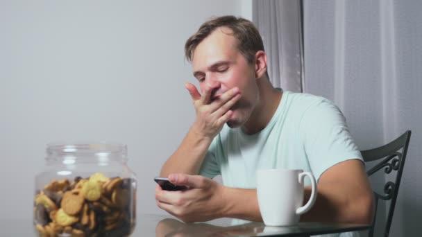 hladová smutný muž sedí v obývacím pokoji u stolu v noci, on jí játra a využívá její smartphone