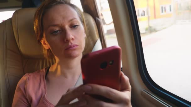Tired woman rides the bus using her phone.