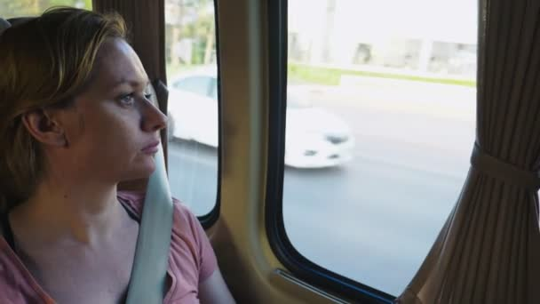 Sad pensive girl riding bus and looking out window