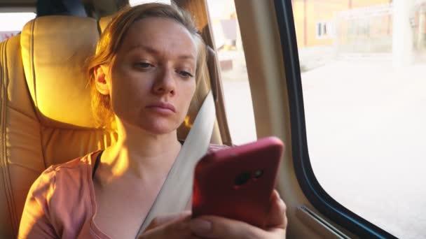 Fáradt nő lovagolni a busz, használ neki telefont.