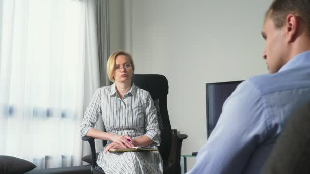 Lékařská koncepce s návštěvou psychologa. žena psycholog poskytuje psychologické poradenství mladému muži