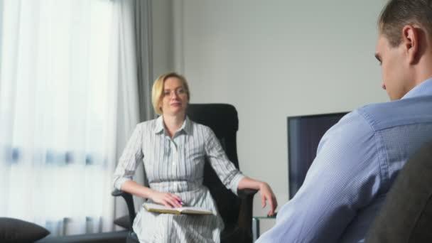 medizinisches Konzept mit Psychologenbesuch. Psychologin berät jungen Mann psychologisch