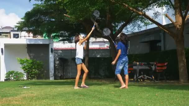 Dospívající chlapec a dívka hrát badminton na zelený trávník na zahradě jejich domu