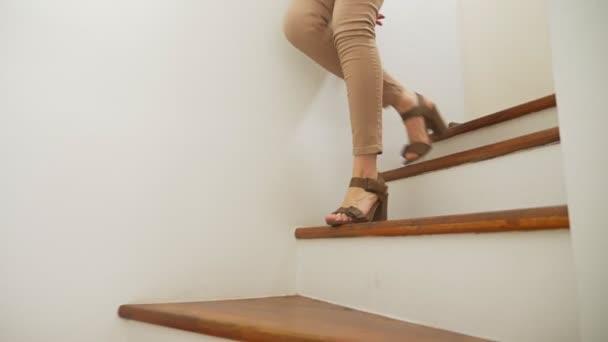 detail, ženské nohy v béžové těsně přiléhající kalhoty a sandály na podpatku chodit po dřevěné moderní schodiště