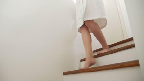 Detail. ženské nohy zvedá vrchol dřevěné schodiště. Žena v županu chodí po schodech