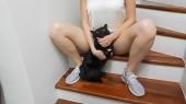das Mädchen sitzt auf der Treppe im Haus zwischen ihren Beinen hält eine schwarze Katze und streichelt sie