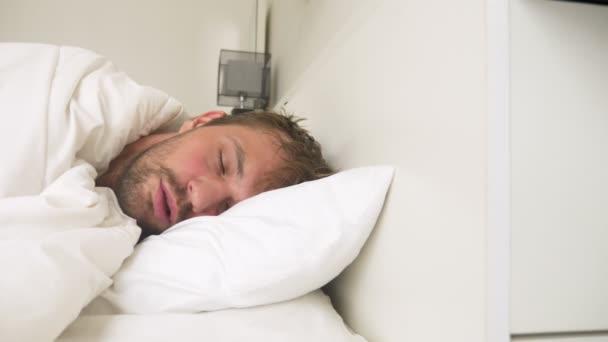 kranker junge Mann mit Fieber schlafend im Bett, von einer Schneedecke bedeckt