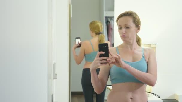 Koncept nadváha a hubnutí. Žena se dívá na sebe do zrcadla a Fotografie její postavu. Chcete-li porovnat výsledky před a po hubnutí.