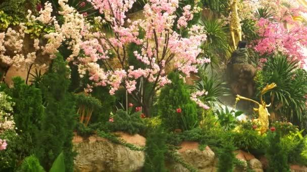 velký umělý vodopád, orámovaná růžovými květy a zelenými listy.