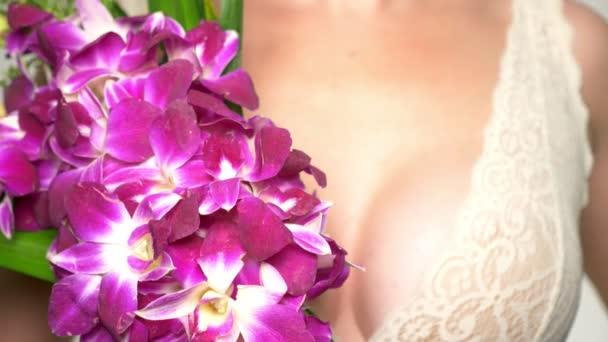 Close-up. weibliche Brust Nahaufnahme mit einem großen Strauß Orchideen in ihren Händen. weibliche Brust Gesundheitskonzept