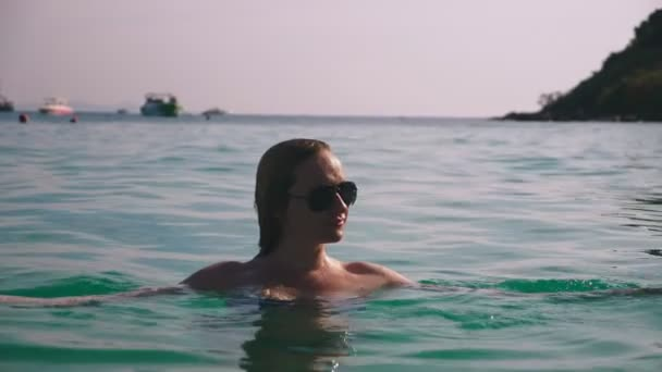 Szőke lány a fürdőruhát és fekete napszemüveg. Szexi test gyönyörű modell úszik a víz kék tenger