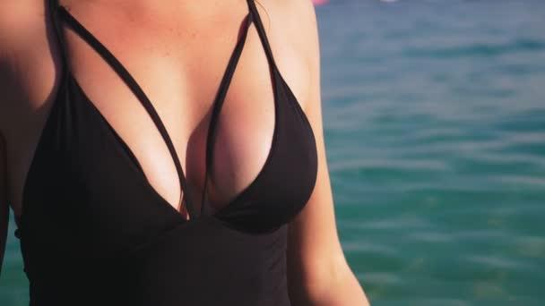ženské poprsí zblízka. Dívka blondýna v černé plavky a černé brýle. Krásný model s sexy tělo se baví v křišťálově čisté mořské vody