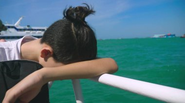 boy teenager suffers from motion sickness while on a boat trip. Fear of traveling or illness of the virus during a cruise holiday.