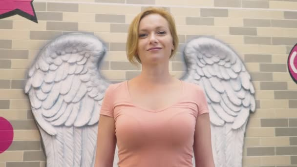 Blonďatá žena stojí na pozadí zeď s basreliéfy v podobě andělská křídla.