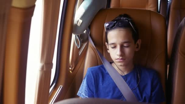 Concept of summer vacation, travel. teen boy rides in a minivan with headphones.