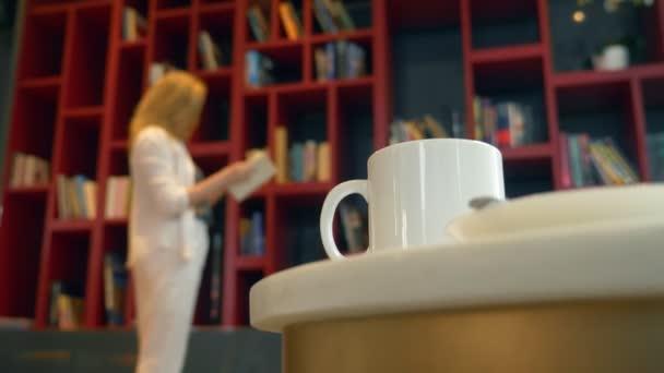 Zaměření na hrnek s horkým nápojem, na stole v knihovně. Rozostření, mladá žena, výběr knihu ke čtení, stojící před knihovna.