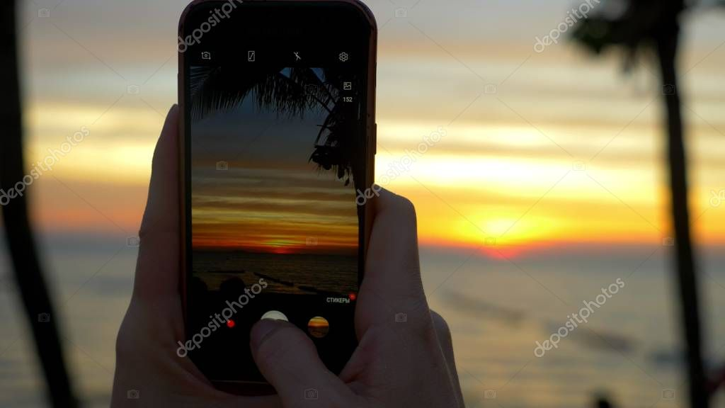 A woman with a mobile phone makes a photo of a tropical beach at sunset.