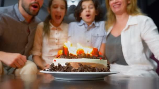 Usmívající se šťastlivce foukání svíčky na její narozeninový dort. děti uprostřed své rodiny. narozeninový dort se svíčkami