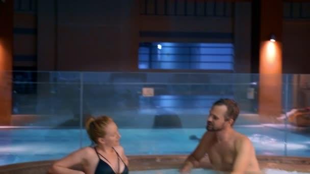 Pár se uvolňuje v venkovní vířivku. Šťastná mladá žena a muž relaxaci v horké vodě u bazénu.