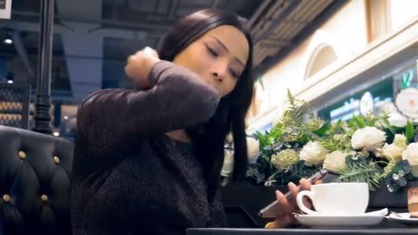 Fiatal, vonzó ázsiai lány, ladyboy mosolyogva és használ neki smartphone, miközben ül egy asztalnál egy kávézóban