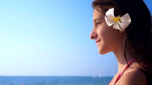 Closeup portrait of brunette girl with plumeria flower in her hair on tropical beach